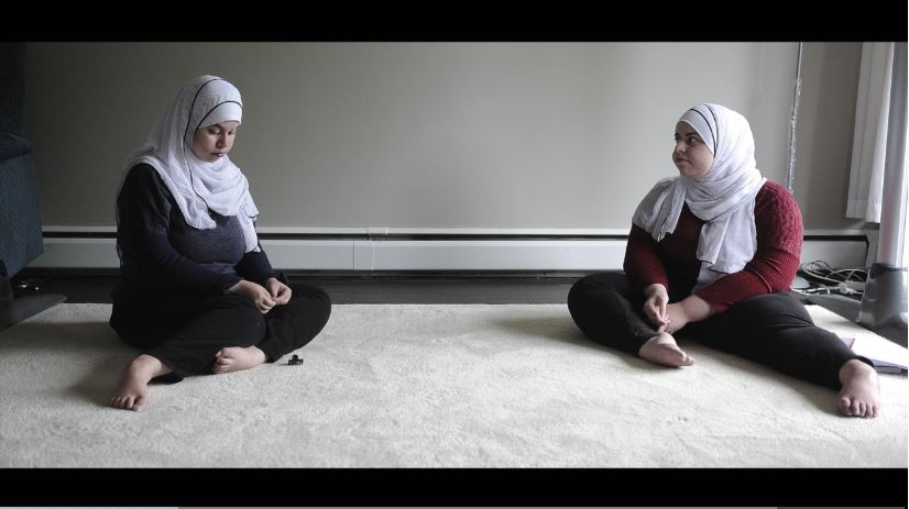 Hoda and Maha Al-Sidawi sitting on floor of Vancouver apartment